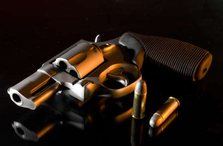 Handgun on a glass bedstand with an orange light from the right side Фото со стока - 12858065
