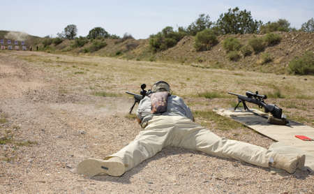 Shooter laying on the ground taking a shot at a target at 100 yards.  版權商用圖片