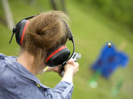 Female at the firing line with a handgun and brass flying Standard-Bild