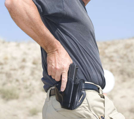 holster: Hand on a handgun about to be pulled from the holster Stock Photo