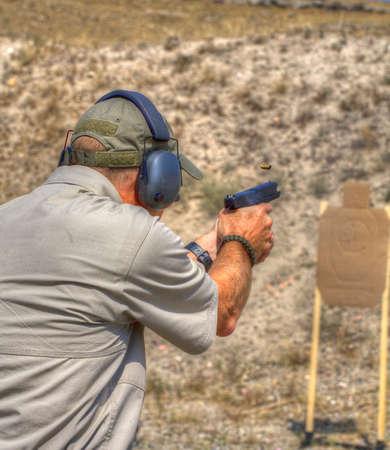 marksman: Marksman practicing at the range with a polymer handgun Stock Photo