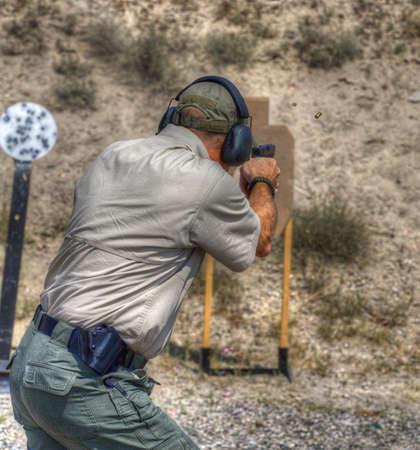 사격장에서 연습하는 권총 사수