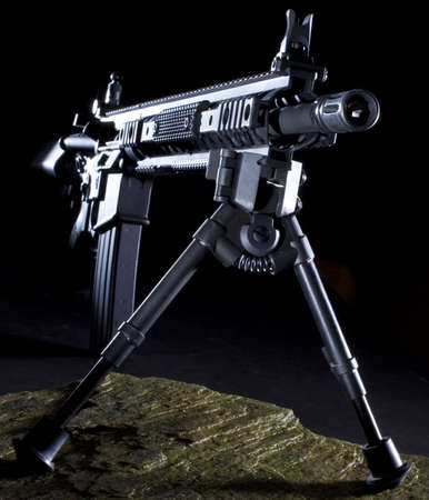 ar: Modern assault rifle with a bipop ready for a long shot from the dark