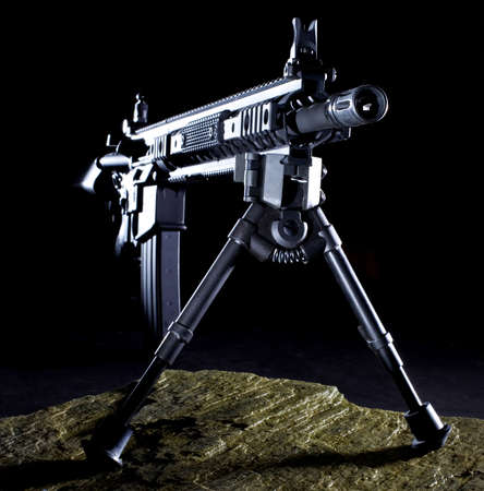 Semi automatic rifle that is set up with a bipod in the dark on a rock
