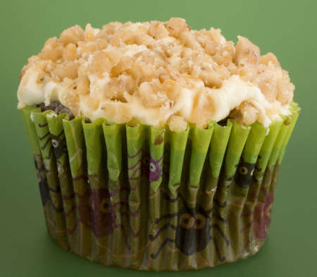 Cupcake with crushed peanuts atop on a green background