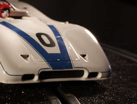 slot car track: White and blue slot car that is making a corner on the track