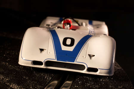 slot car track: Slot car that is making a corner on a dark track