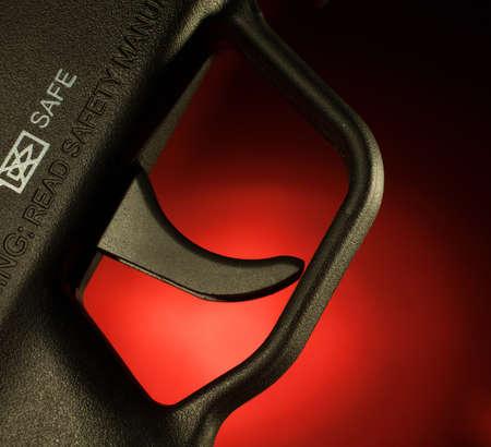 gatillo: Asalto gatillo de escopeta que es con un fondo rojo