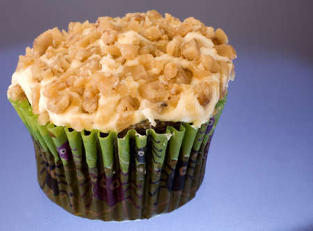 White frosted cupcake that has crushed peanuts atop on blue