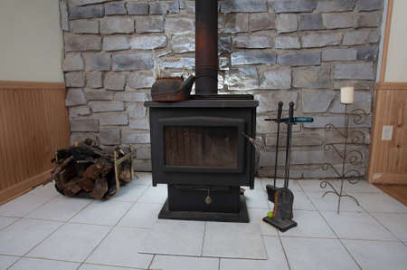 Wood burner in a basement that helps heat the house Archivio Fotografico