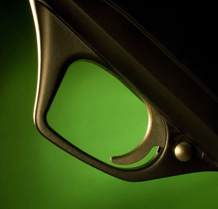 Black trigger on a modern shotgun with a green background