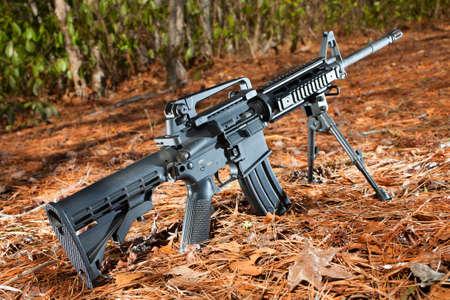 소나무 바늘과 숲 배경에 반 자동 소총 블랙