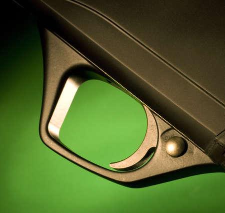 Trigger on a shotgun that is on a green background Reklamní fotografie