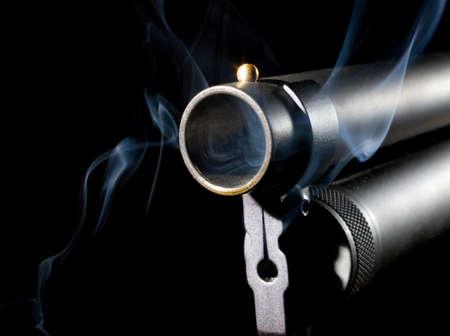 Shotgun barrel that has smoke coming from inside photo