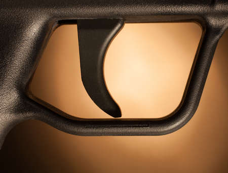 Trigger on an assault rifle with a dark tan background Stock Photo