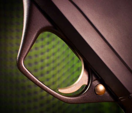 Trigger on a semi automatic shotgun with a green mesh background Stok Fotoğraf