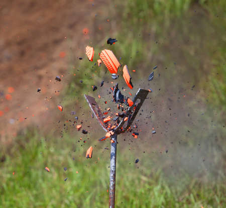 Orange clay target that has just been broken by a shot