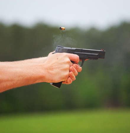 Smoke coming from a handgun and bass after a shot Standard-Bild