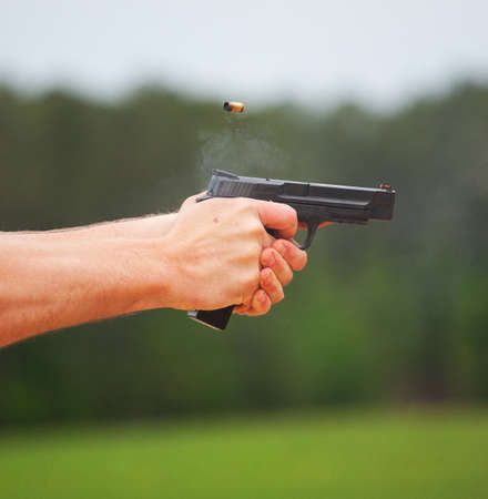 Smoke coming from a handgun and bass after a shot Stock Photo