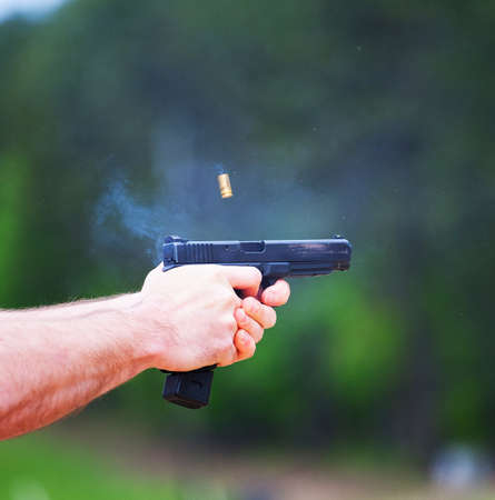 finger on trigger: Semi automatic handgun being shot with brass in the air