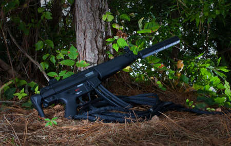 Assault rifle with a short stock and a silencer attached