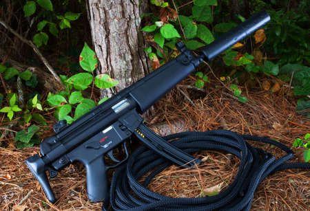 suppressed: Suppressed assault rifle that is at a forest edge