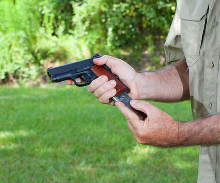 Metal magazine being inserted in a semi automatic pistol