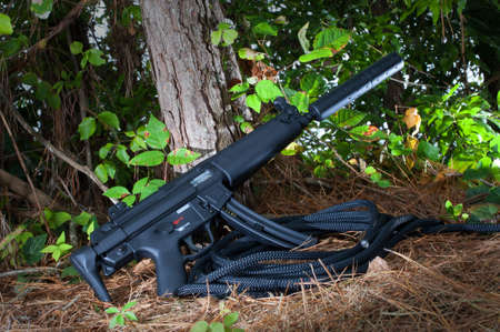 the silencer: Black and short rifle that has a silencer on the end Stock Photo