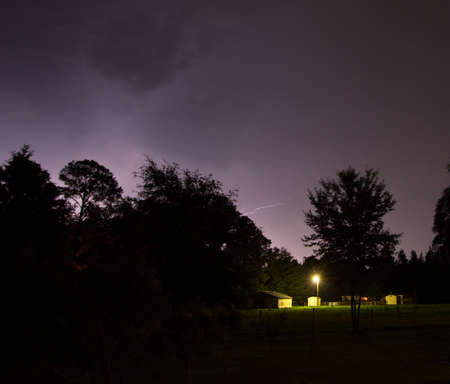 ranch house: Lightning strike in the distance over a small ranch house Stock Photo