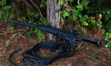 Black assault rifle with an adjustable stock and suppressor