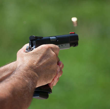 finger on trigger: Brass that has just left a handgun headed at the camera