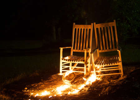 cinders: Rocking chairs on fire with the flames spreading out Stock Photo