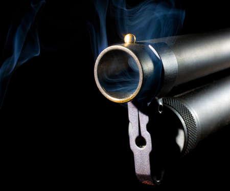 Hot shotgun that has smoke around the muzzle photo