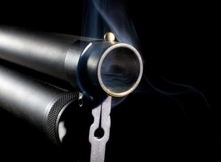 Single barrel from a shotgun that has smoke around it photo