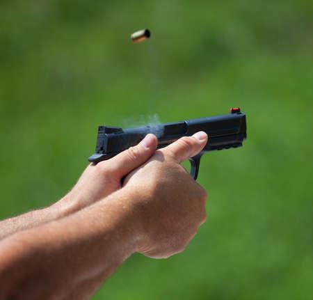 black grip: Left handed shooter after just releasing a shot from a handgun
