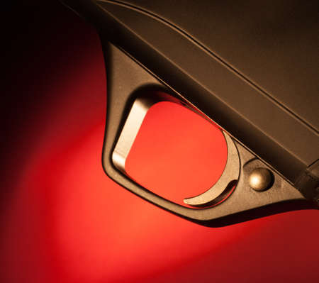 Firearm trigger up close that has a red background