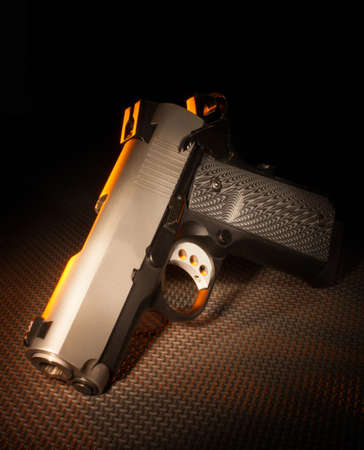 Semi automatic stainless steel handgun with yellow highlights
