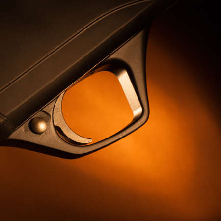 Black shotgun trigger that has a brown background