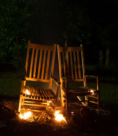 cinders: Two rocking chairs that are on fire and smoking