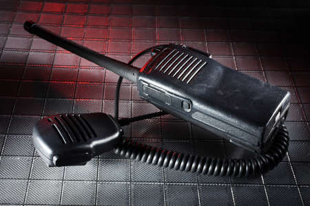 Handheld radio and microphone on a textured background