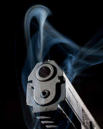 Polymer handgun on a dark background surrounded by smoke