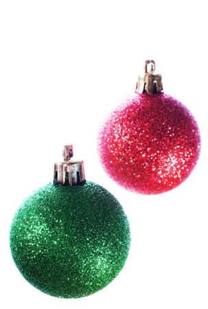Two Christmas tree bulbs suspended in front of a white background Banco de Imagens