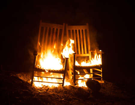 cinders: Two rocking chairs that have been set on fire Stock Photo
