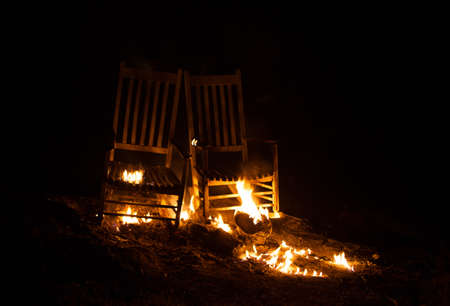 cinders: Pair of rocking chairs that have been added to a fire