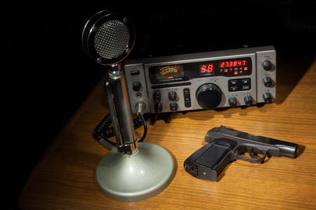 cb: Black handgun on the table with a microphone and two way radio