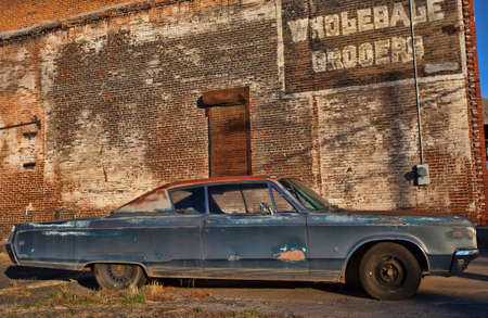 rusty car: Big old and rusty car next to an old building with a mispelling
