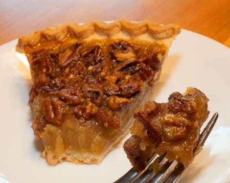 pecan pie: Pastel de nuez en un plato y un tenedor listo para comer