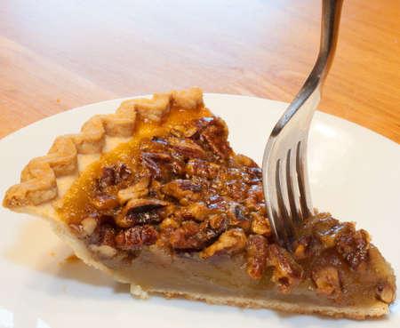 pecan pie: Tenedor de entrar en un pedazo de pastel de nuez en un plato blanco