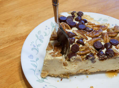 plunging: Fork plunging into a cheesecake with nuts on top