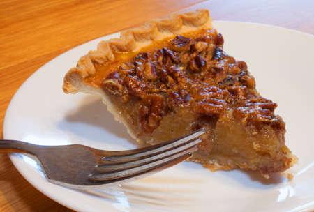 pecan pie: Rebanada de pastel de nuez con un tenedor en un plato blanco Foto de archivo